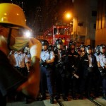 A protester stands in front of policemen outside China Liaison Office during a confrontation in Hong Kong, Chin