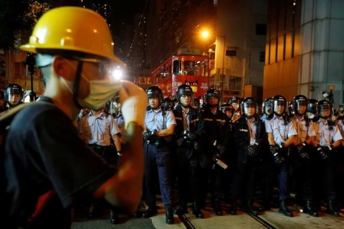 A protester stands in front of policemen outside China Liaison Office during a confrontation in Hong Kong, China November 6, 2016.      REUTERS/Bobby Yip