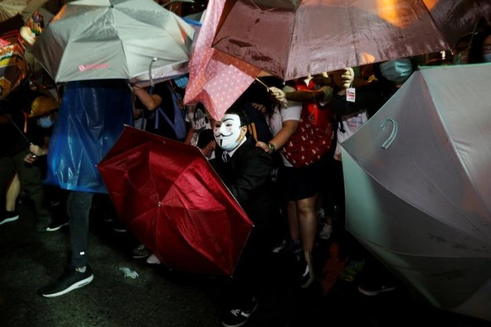 A protester wears Guy Fawkes mask during a confrontation with the police outside China Liaison Office in Hong Kong, China, November 6, 2016.      REUTERS/Bobby Yip