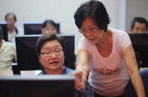 A senior volunteer (R) helps an elderly person during a basic computer course in Singapore June 30, 2016. Under the Infocomm Development Authority of Singapore's Digital Inclusion programme, there are over 100 IT courses available for seniors at the Silver Infocomm Junctions located island-wide. As shown here is the Silver Infocomm Junction at RSVP Singapore, where seniors come together to learn and enjoy the perks of adopting technology to their lives.\n\nMinistry of Communications & Information via Reuters