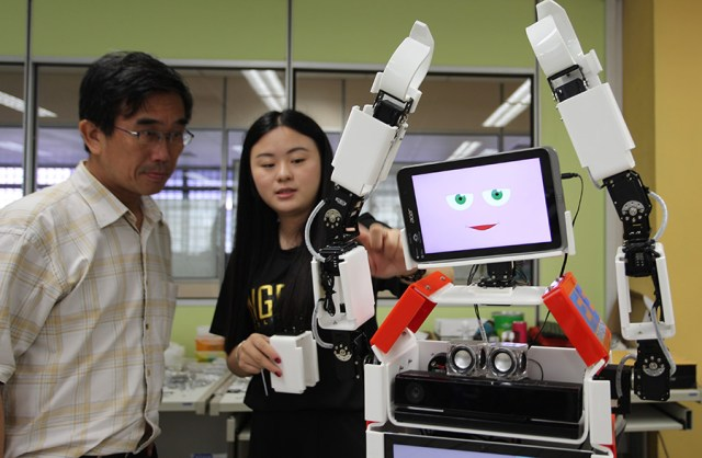 Ng Kwek Kwen, a Technical Support Officer and Zheng Jingjing, a student in the Electrical Engineering Division, Ngee Ann Polytechnic, perform adjustments on a robot named RoboCoach Xuan 2 in the Electrical Product Development Lab in Singapore July 1, 2016. RoboCoach Xuan 2 is a humanoid social robot designed to function as an exercise coach to guide and motivate senior citizens in their physical exercise.\n\nMinistry of Communications & Information via Reuters