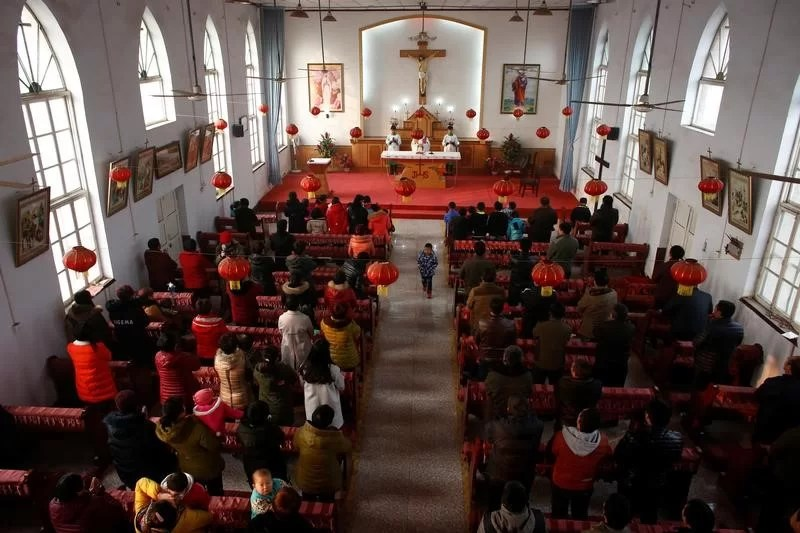 Members of the congregation clean the unofficial catholic church after Sunday service in Majhuang village