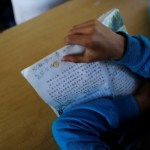A child holds a book during a Chinese language lesson in a school at Namtit, Wa territory in northeast Myanmar