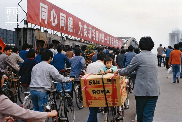 1980s. In the early 80s, the first televisions begin to enter Chinese homes. The image shows a TV color set just bought while being transported in some way at home.