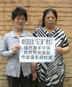 "The sign reads, ""We are women who survived the Masanjia camp. We strongly demand that the Chinese government free the rights-defending author and photographer Du Bin."""