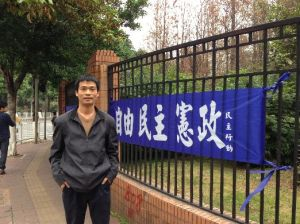 "Liu Yuandong (刘远东) in front of a banner that reads ""Liberty, Democracy, Constitutionalism."""