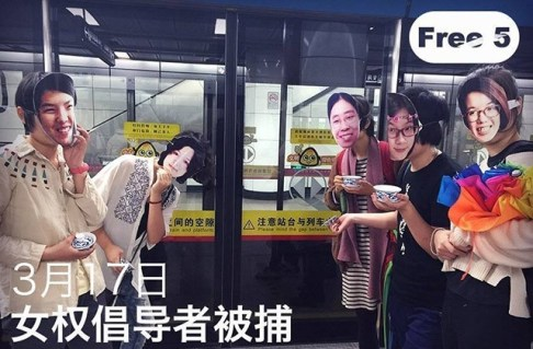"""Masked activists pose on a subway with tea cups. Being """"invited to drink tea"""" is a common euphemism Chinese authorities use for bringing activists in for interrogation. Credit: China File."""