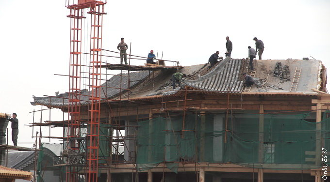 workers on roof of chinese looking building