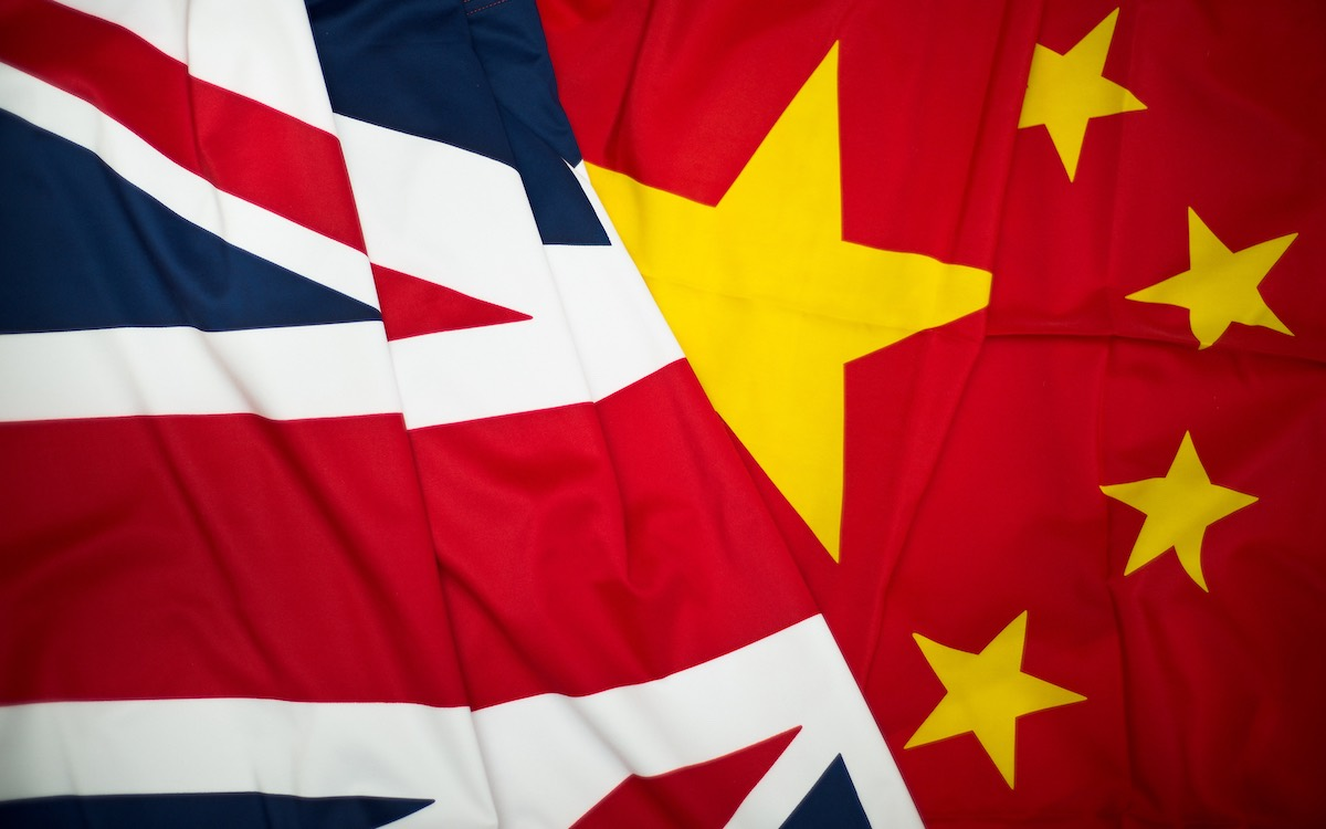 The image shows flags of the UK and China intertwined. Relations between the two countries have reached a new low.
