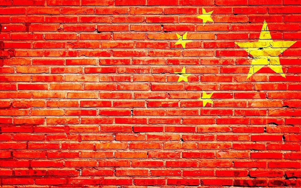 The image shows a Chinese flag imposed on a brick wall to illustrate China's Great Firewall. Clubhouse managed to breach the censors before the audio app was closed down.