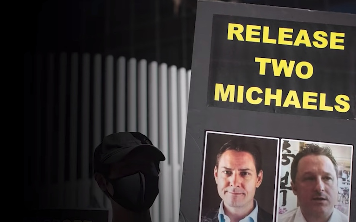 """A dark image of a protester holding up a placard demanding the release of the """"Two Michaels."""" Canadians Michael Spavor and Michael Kovrig are facing alleged espionage charges."""