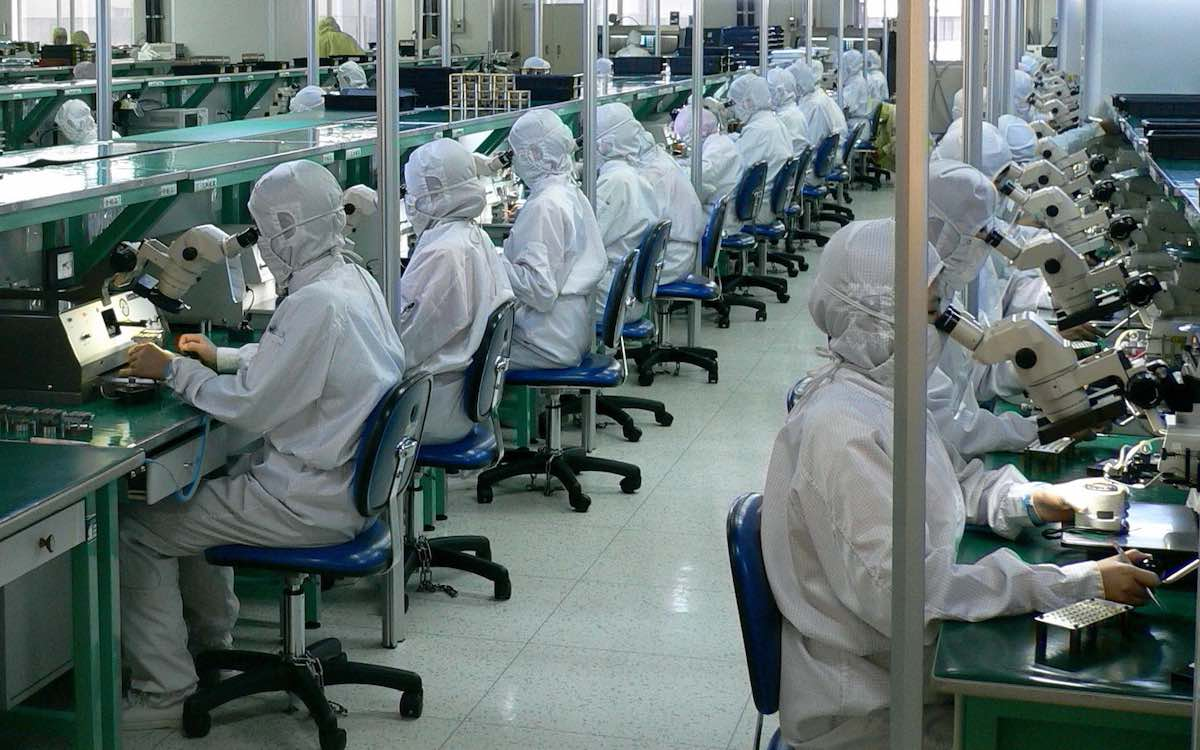 The image shows rows of workers in blue dust suits testing fiber optics. China needs to break through technology barriers to become a great manufacturing power.