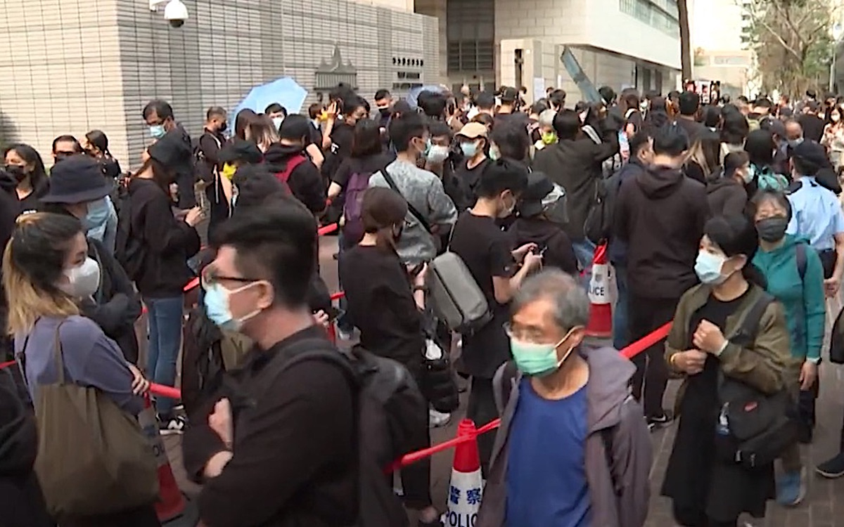 The screenshot shows a pro-democracy protest outside a Hong Kong court. Up to 1,000 gathered to support 47 activists that appeared in court under the Beijing-imposed national security law.