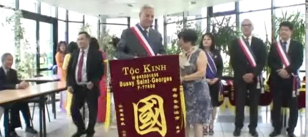 Thị-trưởng-Bussy-St-Georges cầm-cờ-Quốc-gia-Kinh