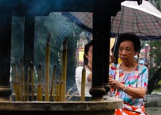 A woman burns incense at Polin Monastery