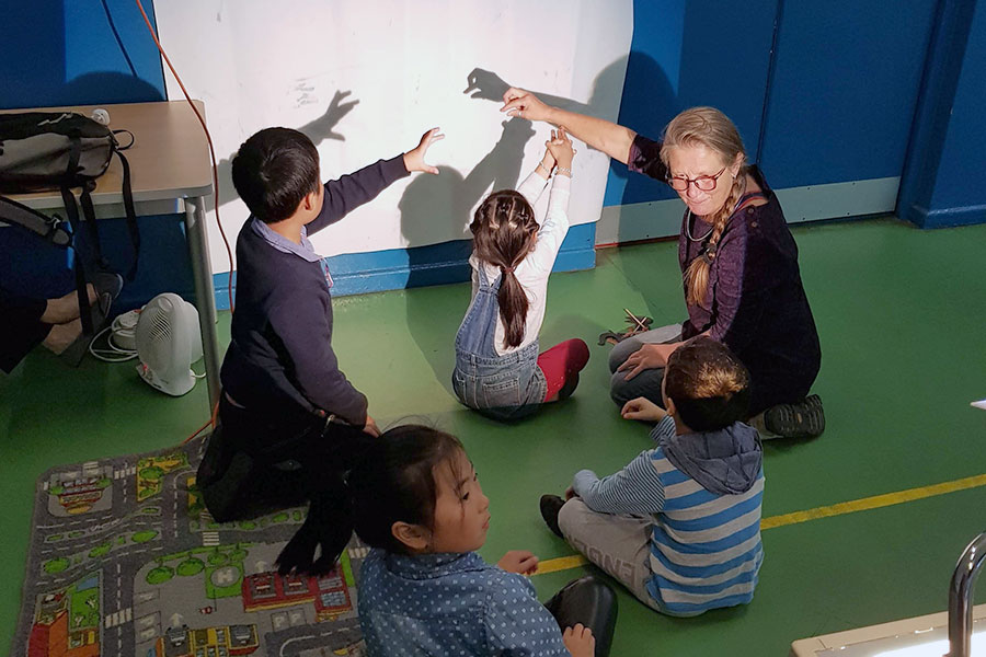 Anna Read shows children at the Lancaster Hua Xian Chinese School shadow puppetry in the lead up to Light Up Lancaster