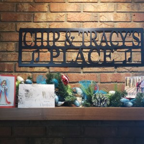 a picture of our fireplace mantel with christmas cards and garland and our metal lazar cut sign that reads chip and tracy's place