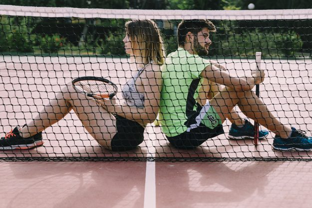 tennis elbow players taking break sitting by the net
