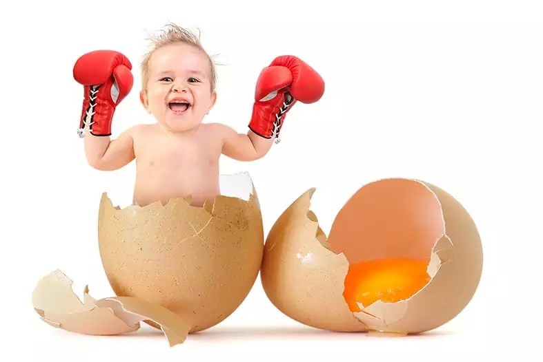 Beautiful baby boy with boxing gloves breaking the egg