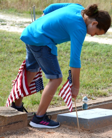 Prior to Memorial Day, Leah Dejesus places a flag at a service man's grave at Iredell's Mitchell Cemetery May 23.