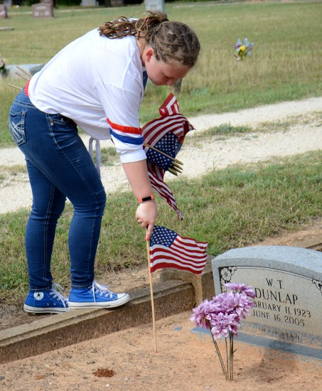 Prior to Memorial Day, Riley Gentry places a flag at a service man's grave at Iredell's Mitchell Cemetery May 23.
