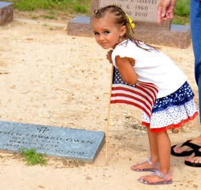Prior to Memorial Day, Gracey Dejesus places a flag at a service man's grave at Iredell's Mitchell Cemetery May 23.