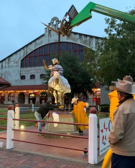Bruce Greene's sculpture of his friend Red Steagall being placed at the Forth Worth Stockyards.