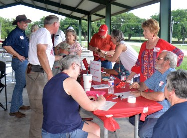 Volunteers Bosque County Judge Don Pool and his wife Jo sign in visitors at the Bosque County Republican Club Party in the Park event June 16.