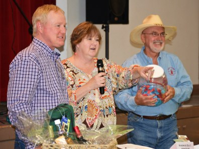 Former Meridian Public Library President and George Hallmark assist Jewels and Jeans auctioneer Todd Clift during a fundraising auction for the library.