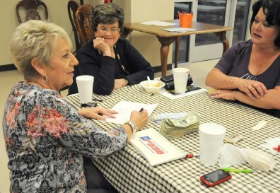 Former Meridian Public Library Treasurer Jimmie Lou Lewis, founding member/ former Board President Mary Beth McMahon and former board President Teresa McMahon count the donation from a Fall Chili Supper.