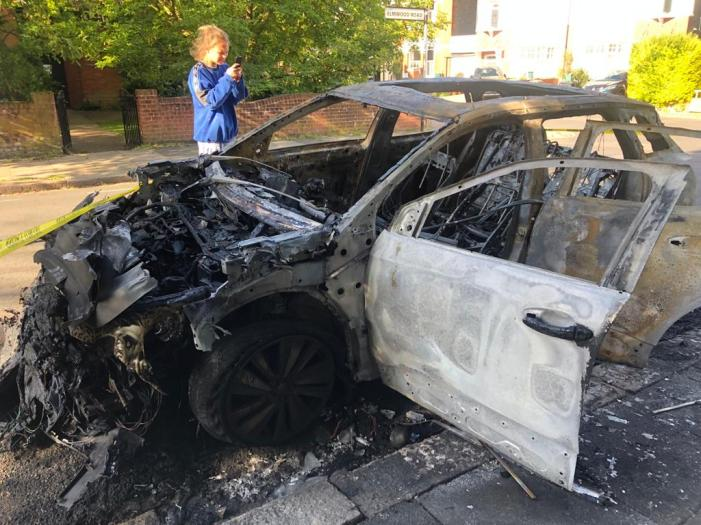 Burnt out car being photographed