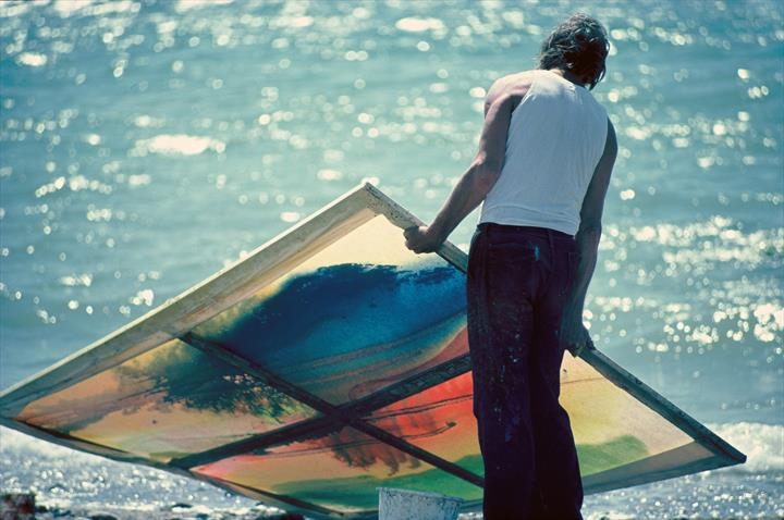 Hoare, J on the beach painting with the se