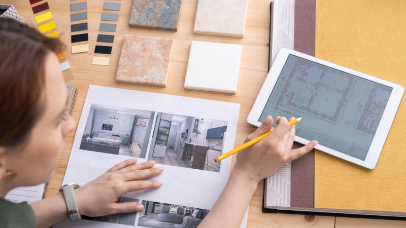 Creative female designer of interior looking through apartment plan in digital tablet and choosing example of photo by workplace