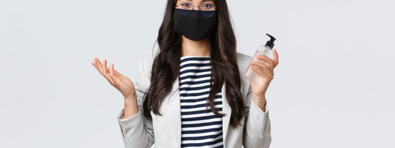 Business, finance and employment, covid-19 preventing virus and social distancing concept. Asian businesswoman, office worker in face mask asking to use hand sanitizer, looking after hygiene.