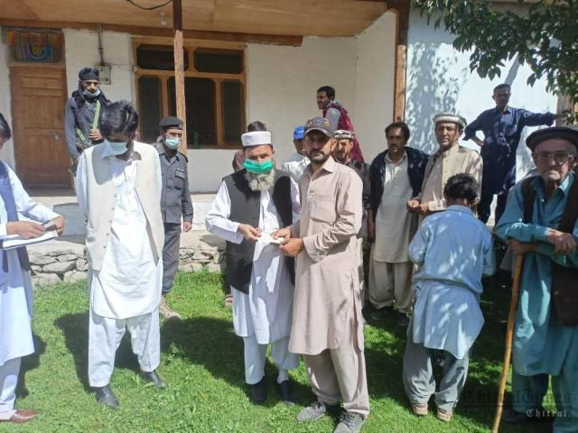 chitraltimes dc upper chitral visit brep distribute cheque among flood effectees3