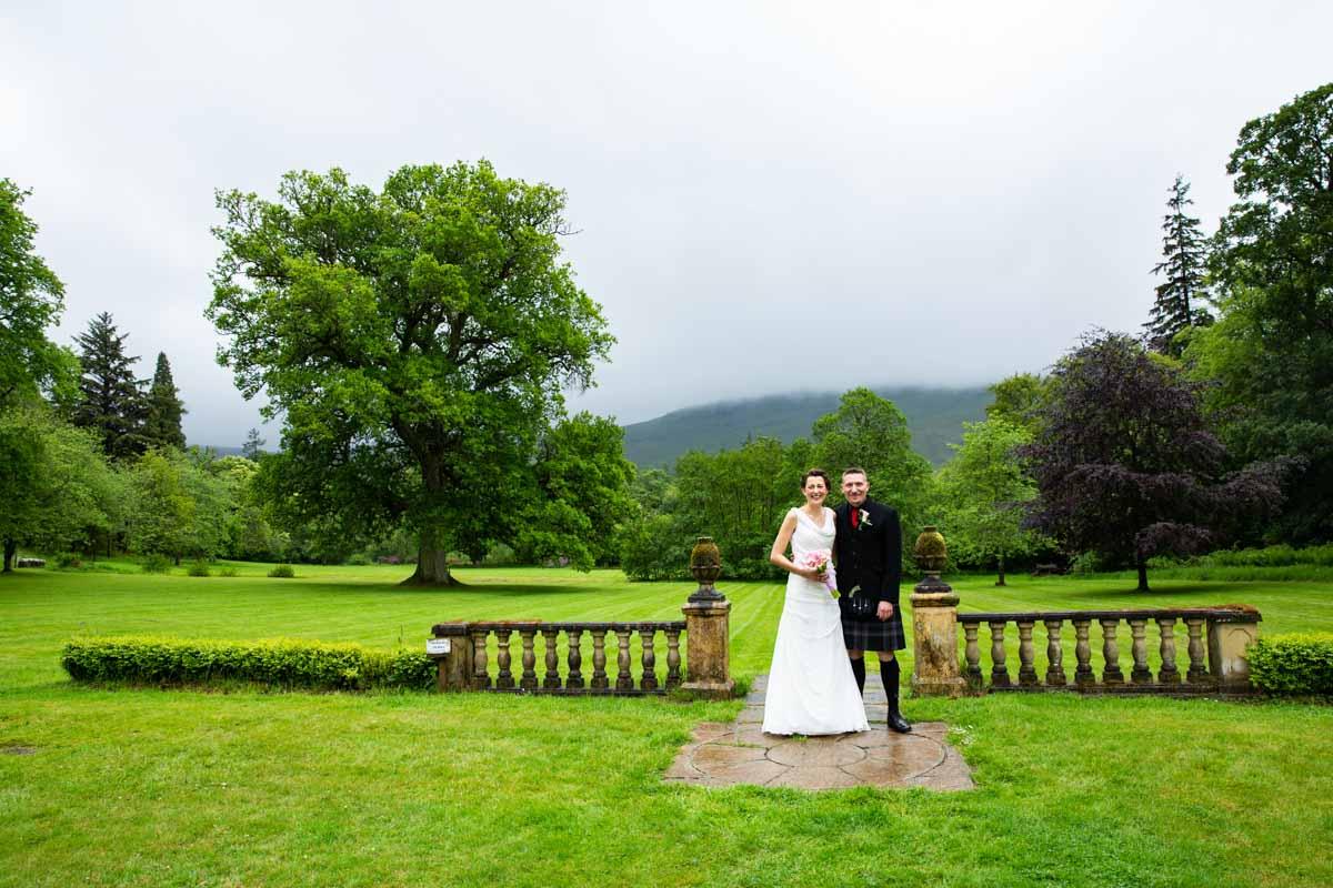 Bride and groom in gardens at Culcreuch Castle wedding venue.