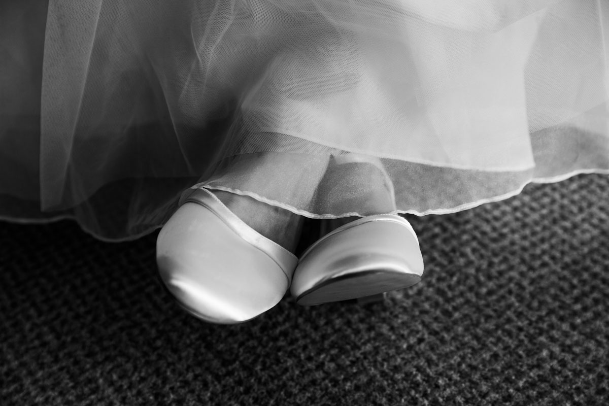 The brides shoes showing under her wedding dress at MacDonald Forest Hills Hotel & Spa