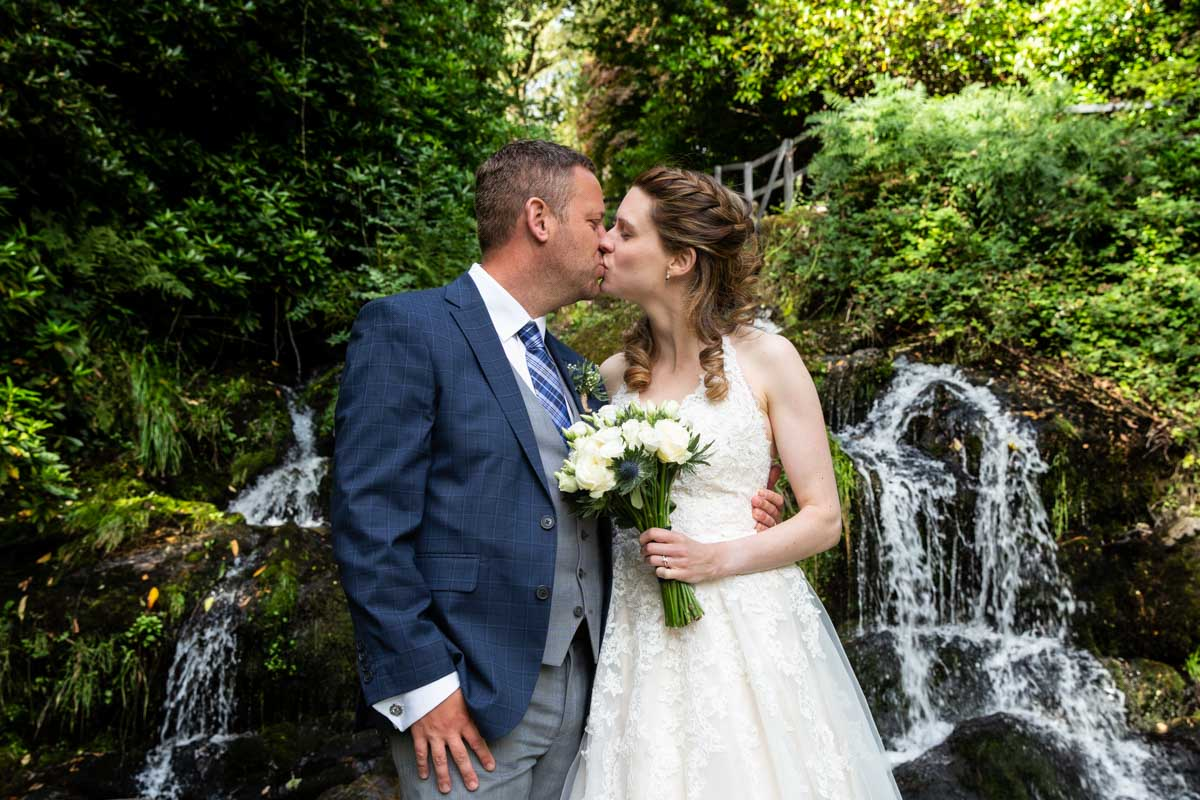 Bride and groom kissing at waterfall MacDonald Forest Hills Hotel