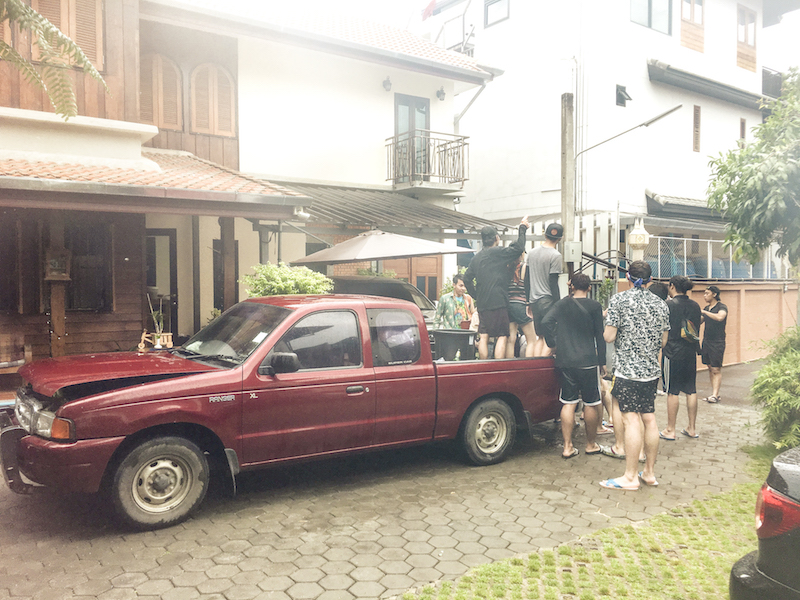 In the hotel yard, people are getting ready to go out on a truck for Songkran water fight.