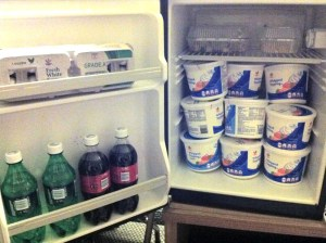 A hotel room fridge, with some sodas in the door and nine tubs or whipped topping defrosting in the main section