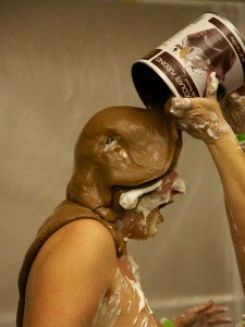 Mistress Messiér gets a coating of chocolate pudding over her head to replace her missing trashbag top at the Debauchery 2012 messyplay demo.