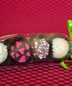 A cellophane sleeve containing four assorted truffles, tied with a ribbon bow.
