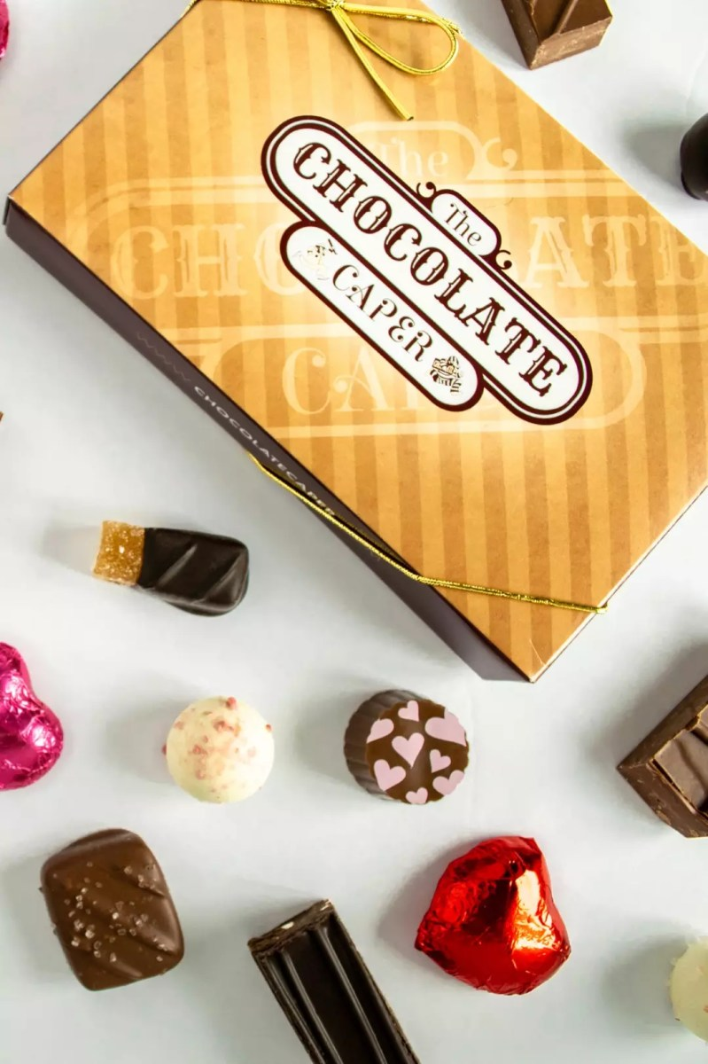 A Chocolate Caper box lid surrounded by assorted chocoalates including pralines, caramels, truffles and gels.