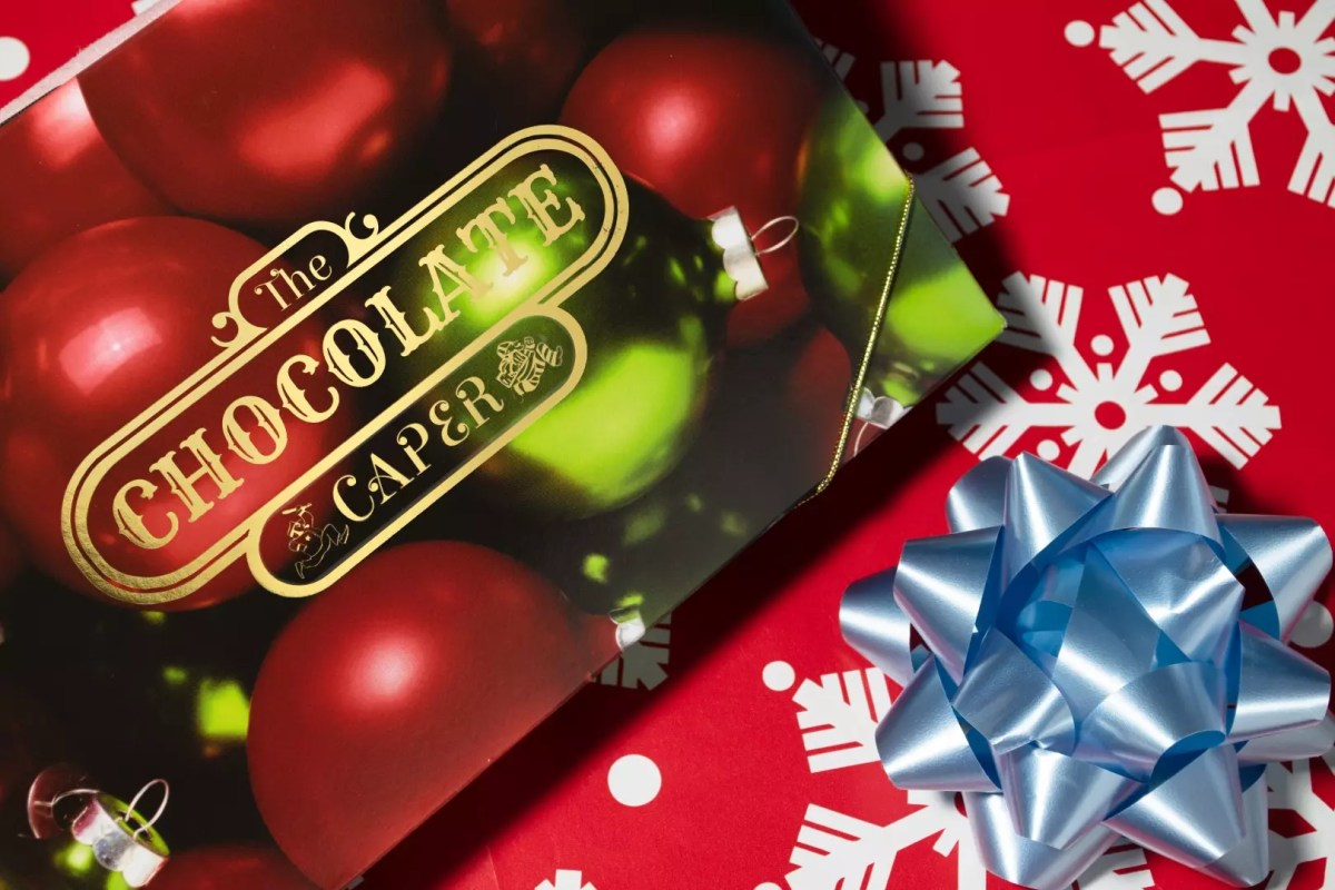 A holiday themed chocolate caper box sitting on a wrapping paper background with a bow