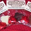 "Three ""From Wisconsin with Love"" packets containing chocolate hearts and chocolate shaped Wisconsins fanned out on a red background, one each in milk, dark and white chocolate."