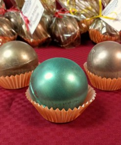 Three hot cocoa bombs - magic drinking chocolate - in front of a row of bagged orbs.