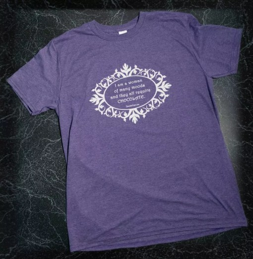 """A heathered purple t-shirt with the words """"I am a woman of many moods, and they all require chocolate"""" in white on the front."""
