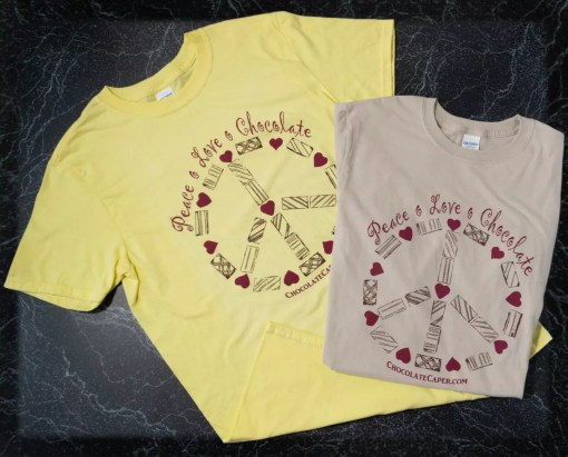 """Sandstone and yellow t-shirts with the words """"Peace Love Chocolate"""" above a peace sign made of candies in red/brown on the front of the shirt."""