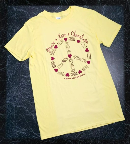 """A yellow t-shirt with the words """"Peace Love Chocolate"""" above a peace sign made of candies in red/brown on the front of the shirt."""