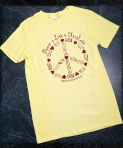 "A yellow t-shirt with the words ""Peace Love Chocolate"" above a peace sign made of candies in red/brown on the front of the shirt."